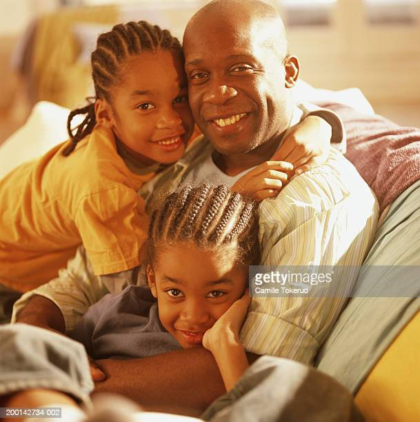 Father and twin sons (6-8) hugging on couch, portrait