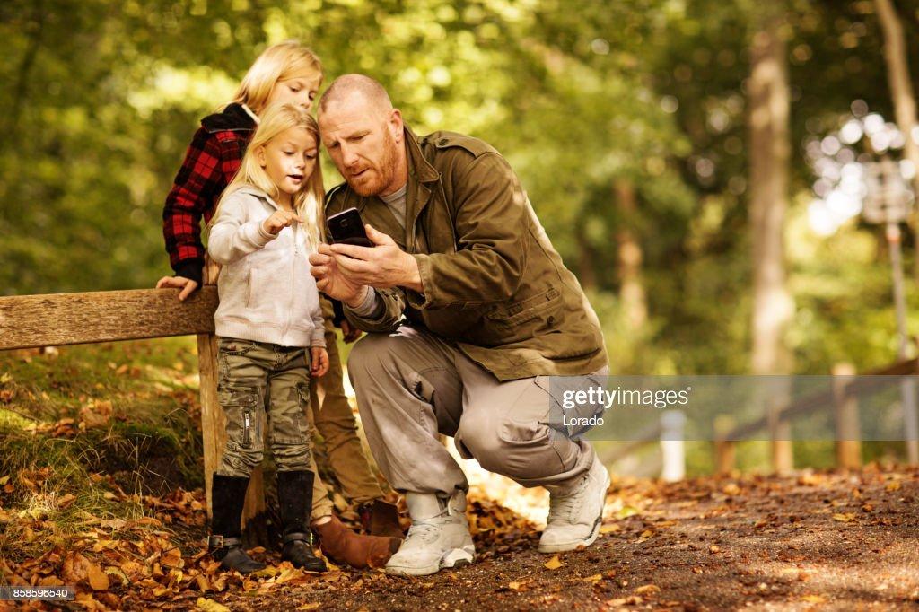 Vater und zwei schöne junge blonde Schwestern in Autumnal Park : Stock-Foto