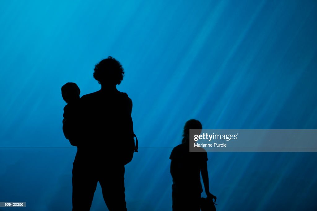 Father and two children at aquarium : Stock Photo
