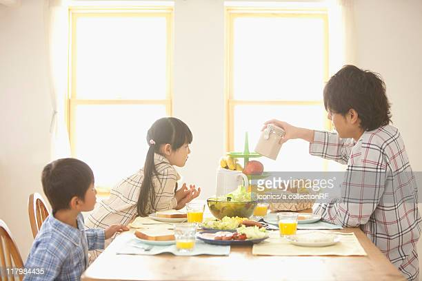 Father and Two Children at Breakfast Table