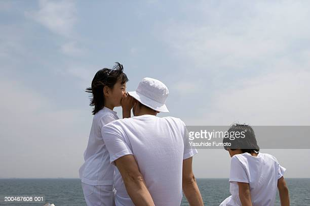 Father and two children (8-10) beside sea, rear view