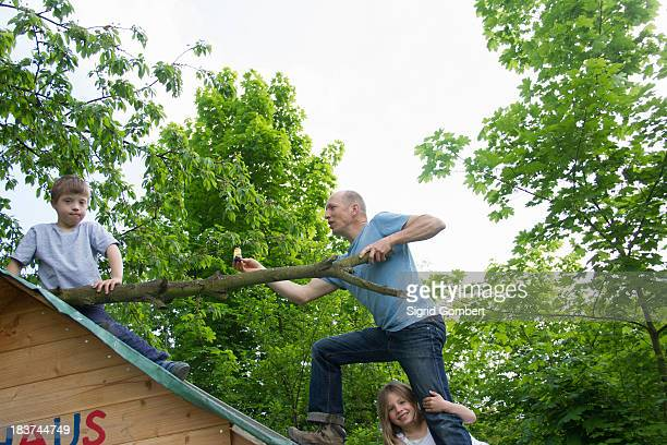 Father and two children climbing on playhouse roof