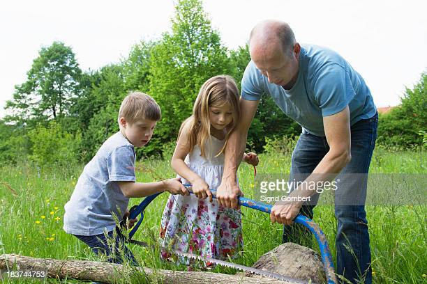 Father and two children learning to use hacksaw