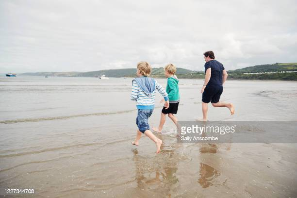 father and two children running in the sea together - coastal feature stock pictures, royalty-free photos & images