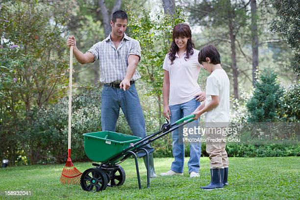 Father and two children working together in yard