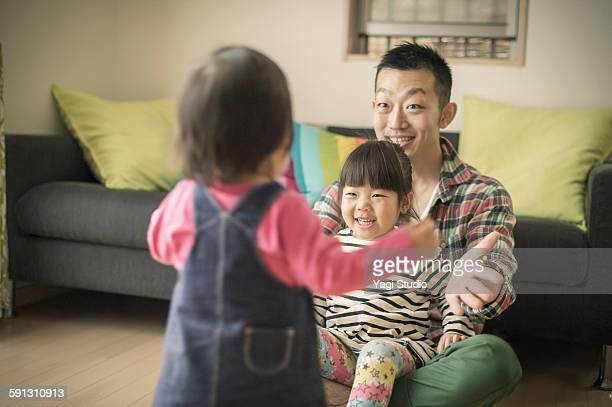 Father and two daughter relaxing in room