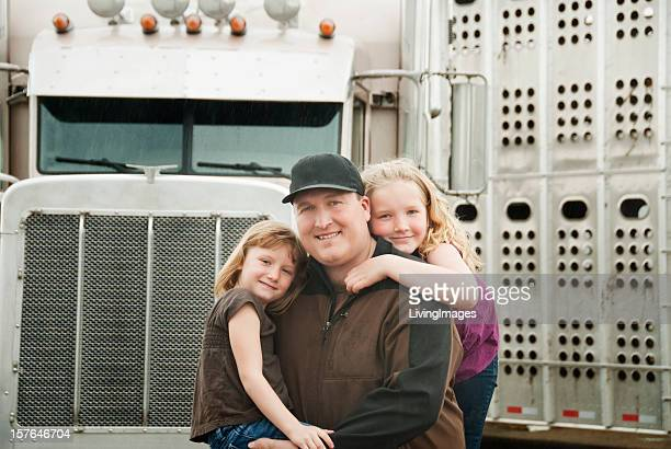 Father and two daughters on the front of a truck, smiling