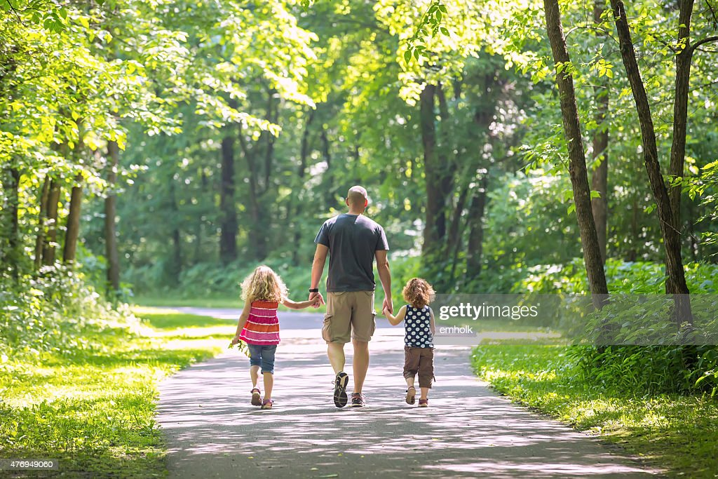 Father And Two Daughters Walking Through Woods at Park : Stock Photo