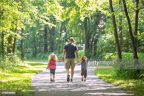 Father And Two Daughters Walking Through Woods at Park