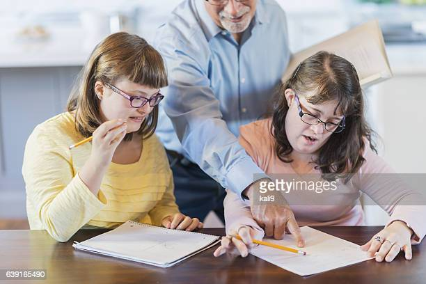 Father and two daughters with down syndrome, homework