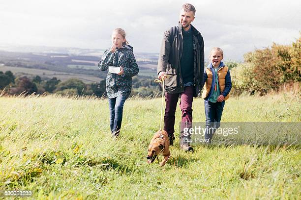 Father and two girls walking dog in field