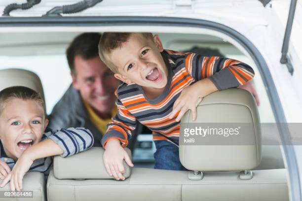 Father and two little boys inside car