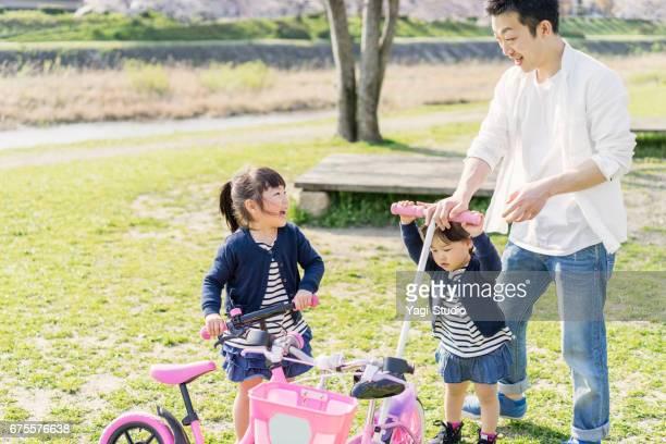 父と 2 人の姉妹が楽しい時を過す時間屋外で。