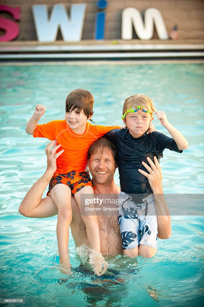 father and two small boys in swimming pool : Stock Photo