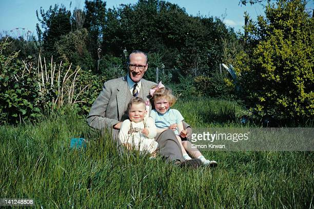 Father and two small daughters in garden