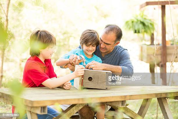 father and two sons building birdhouse outdoors. family time! - birdhouse stock pictures, royalty-free photos & images