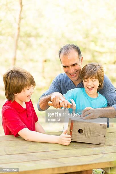 Père et ses deux enfants bâtiment cabane à oiseaux en plein air. Du temps en famille !