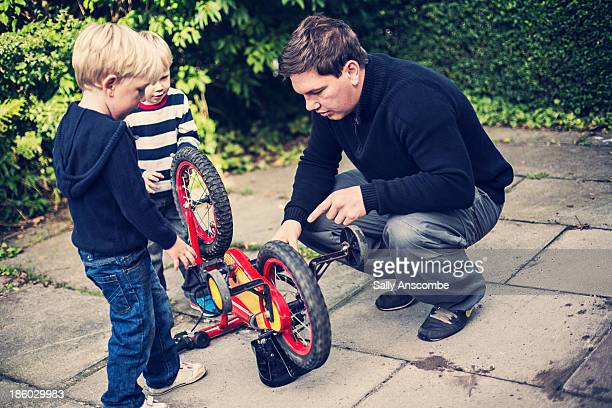 Father and two son's fixing a bicycle