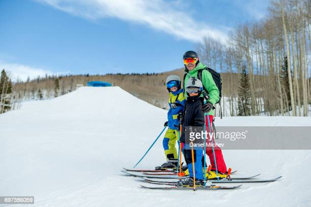 Father and two sons on a ski run.
