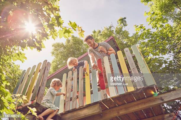 father and two sons, painting tree house, low angle view - tree house stock pictures, royalty-free photos & images