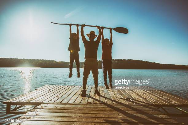 father and two sons playing on pier. - masculinity stock pictures, royalty-free photos & images