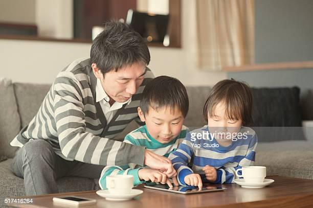 父と 2 つの息子と遊ぶデジタルタブレットて、