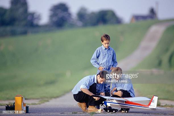 Father and two sons (10-11) (13-14) preparing remote control plane in field