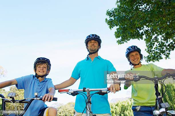Father and two sons (10-12) riding bikes in park, smiling, low angle
