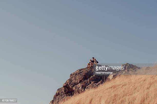 Father and two sons sitting on rocks, Mount Tamalpais, California, America, USA