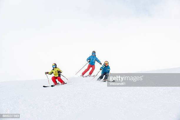father and two sons skiing together - ウィンタースポーツ ストックフォトと画像