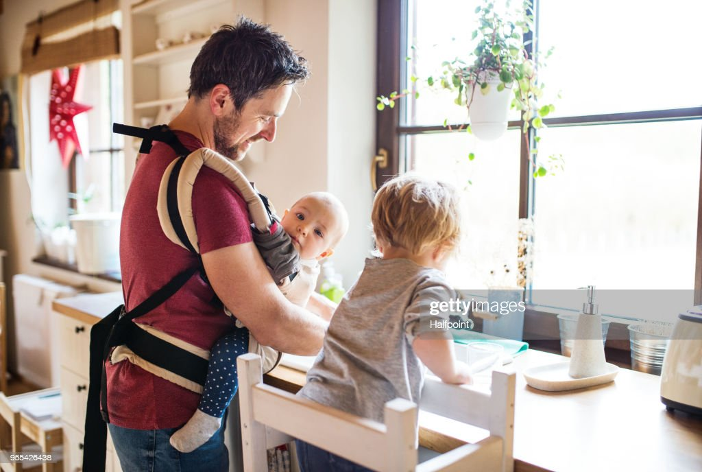 Father and two toddlers washing up the dishes. : Stock Photo