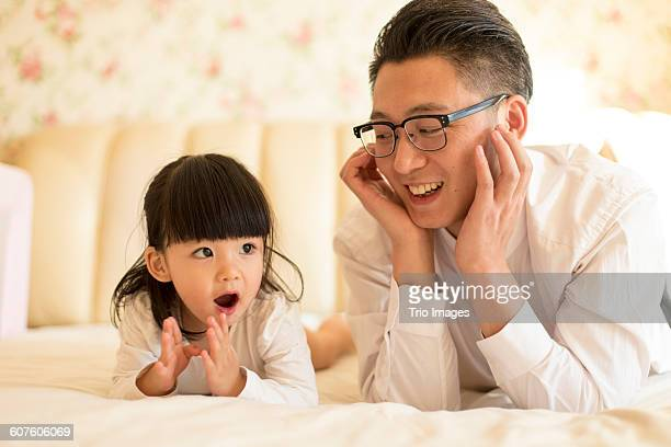 father and two years old little daughter on bed - 30 34 years stockfoto's en -beelden