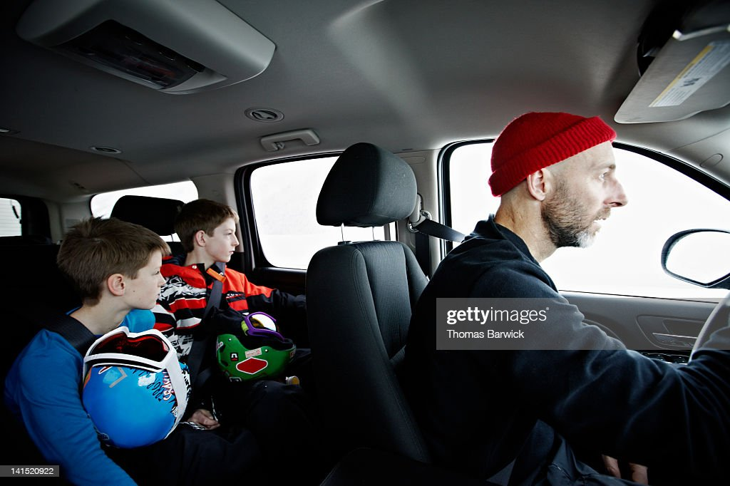 Father and two young sons riding in car : Stock Photo