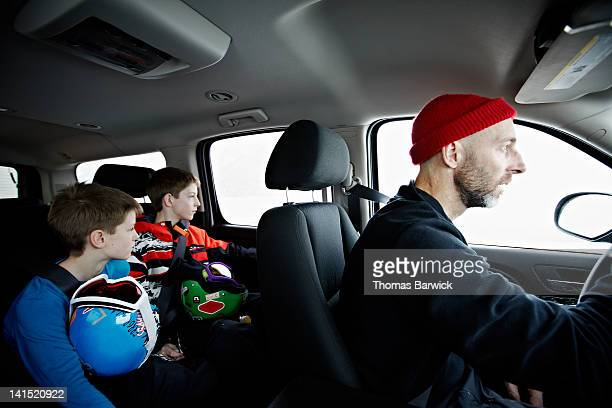 father and two young sons riding in car - family inside car stock photos and pictures