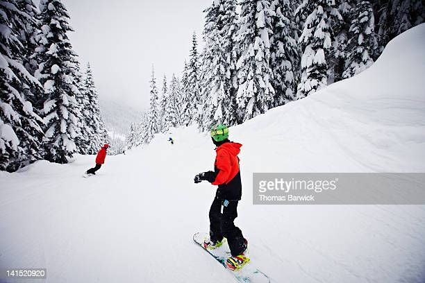 Father and two young sons snowboarding downhill
