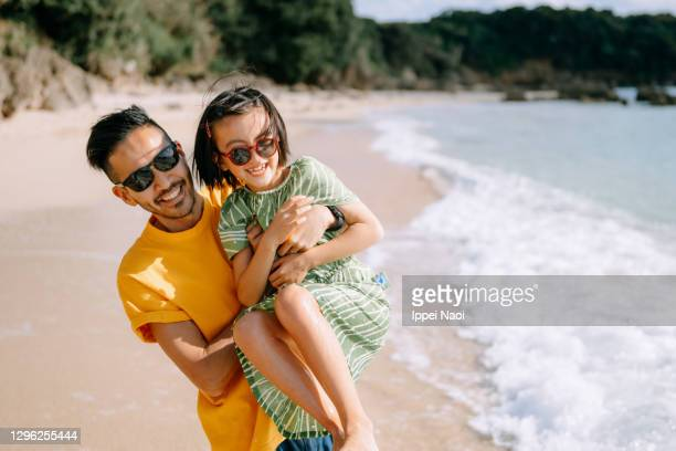father and young daughter having fun on beach, japan - サングラス ストックフォトと画像