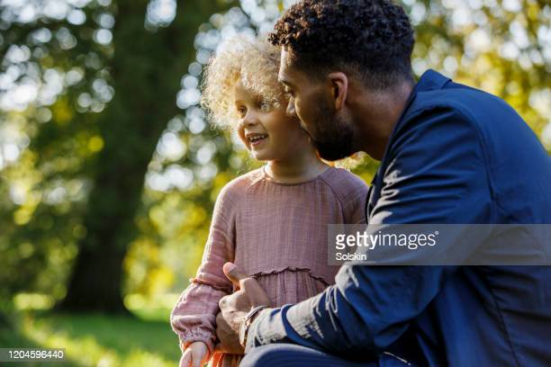 father and young daughter in park area - genderblend stock-fotos und bilder