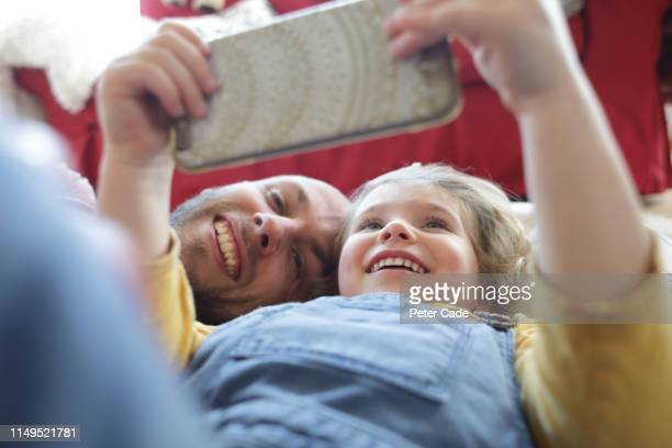 father and young daughter laying down, looking at phone - small stock pictures, royalty-free photos & images