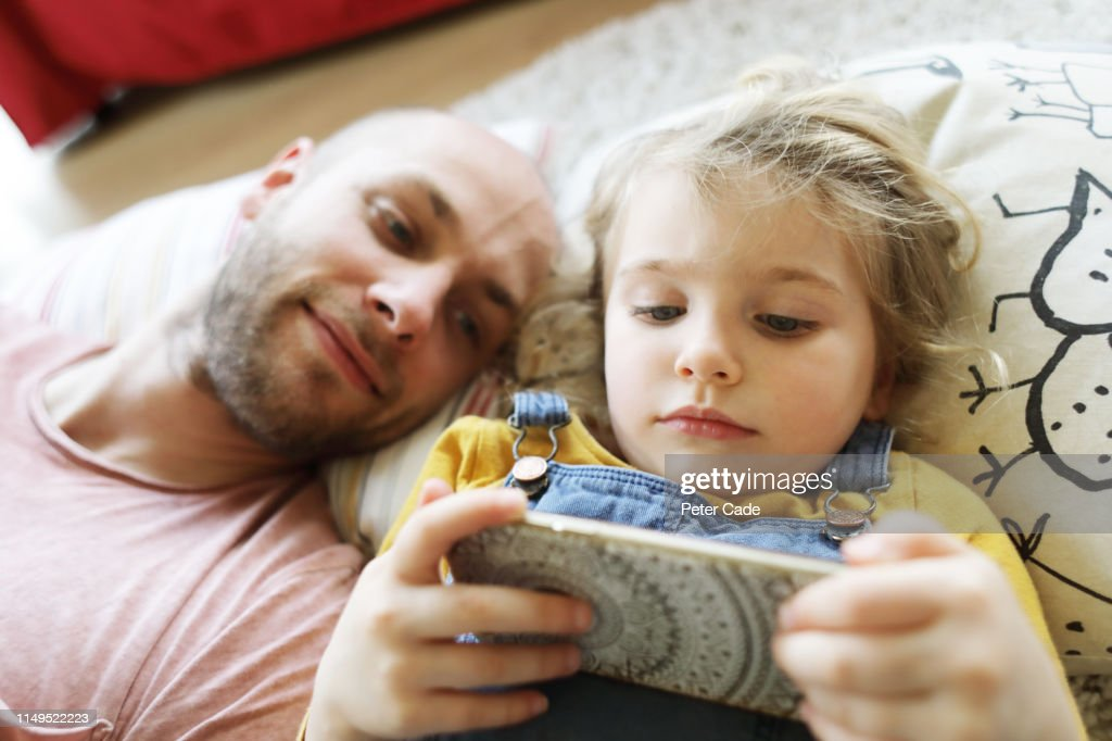 Father and young daughter laying down, looking at phone : Stock Photo