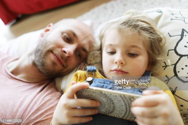 father and young daughter laying down, looking at phone - portability stock pictures, royalty-free photos & images