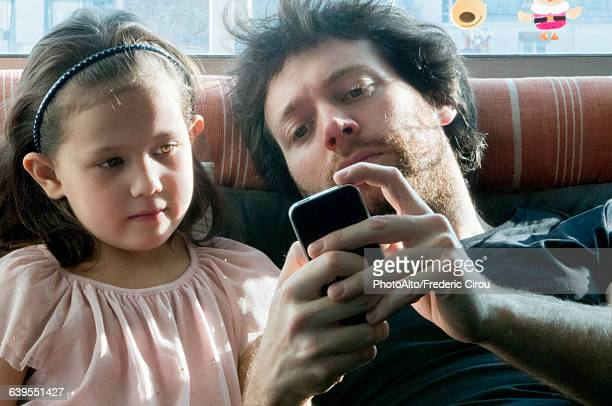 father and young daughter looking at smartphone together - close to stock pictures, royalty-free photos & images