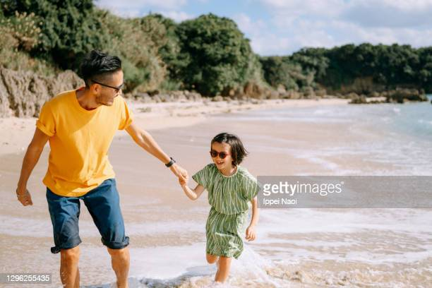 father and young daughter running together on tropical beach - tropical climate stock pictures, royalty-free photos & images