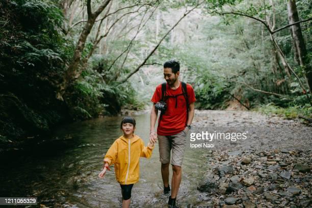 father and young girl hiking in forest river, okinawa, japan - reality fernsehen stock pictures, royalty-free photos & images