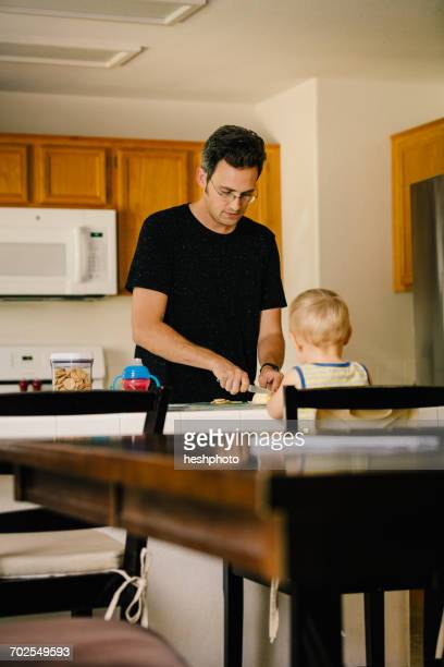 father and young son at home, father preparing food - heshphoto fotografías e imágenes de stock