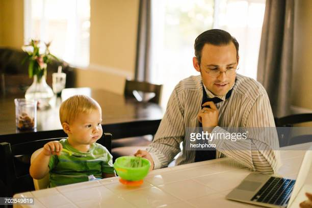 father and young son at kitchen table, son eating breakfast, father putting on neck tie, looking at laptop - heshphoto stock pictures, royalty-free photos & images