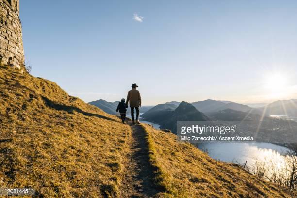 father and young son explore a mountain path above a lake at sunrise - beauté de la nature photos et images de collection