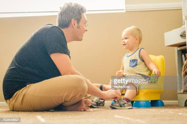 father and young son, face to face, father dressing son - heshphoto stockfoto's en -beelden