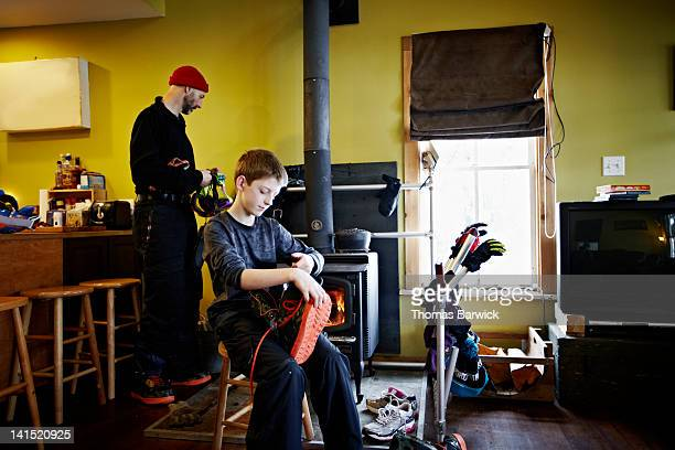 Father and young son in cabin by wood stove