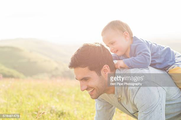 Father and young son in field, father carrying son on back