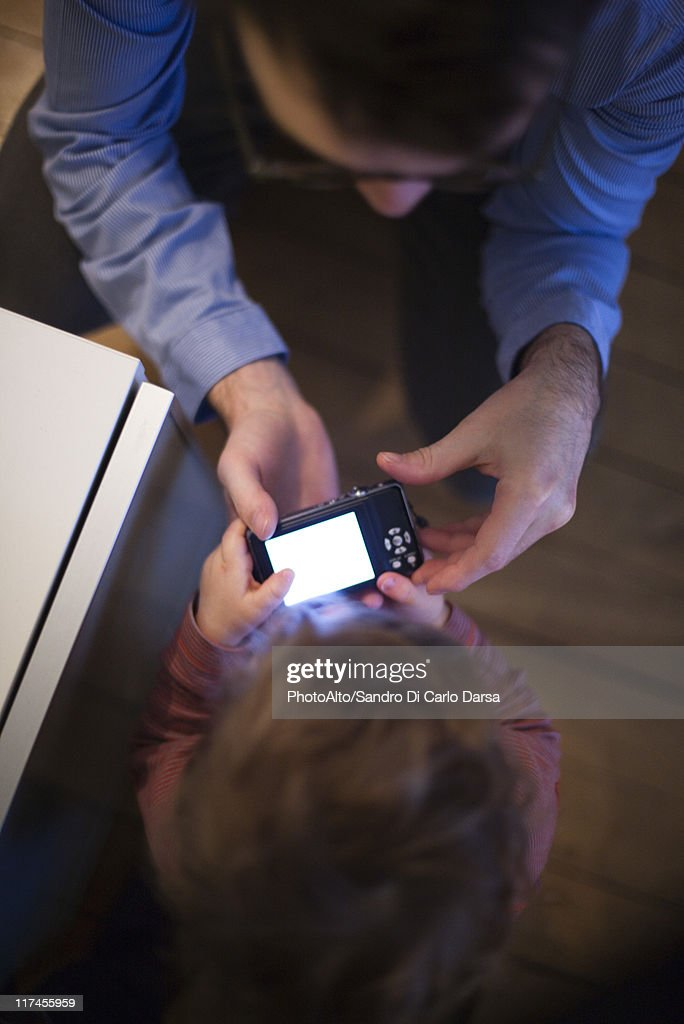 Father and young son looking at digital camera together, overhead view : Stock Photo